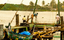 Ancient Chinese Nets Of Fishermen That Are Still Used And Reflected On The Sea, Together With Fishermen And Diverse Local People, In A Calm Rural Village Landscape Of The Southern Indica, Asia