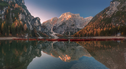 Lago di Braies scenic autumn panorama. Beautiful lake with boats and mountains reflection. Pragser Wildsee, South Tyrol, Italy