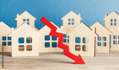 Fototapeta Real Estate Market Falls. Red arrow down on the background of houses obraz