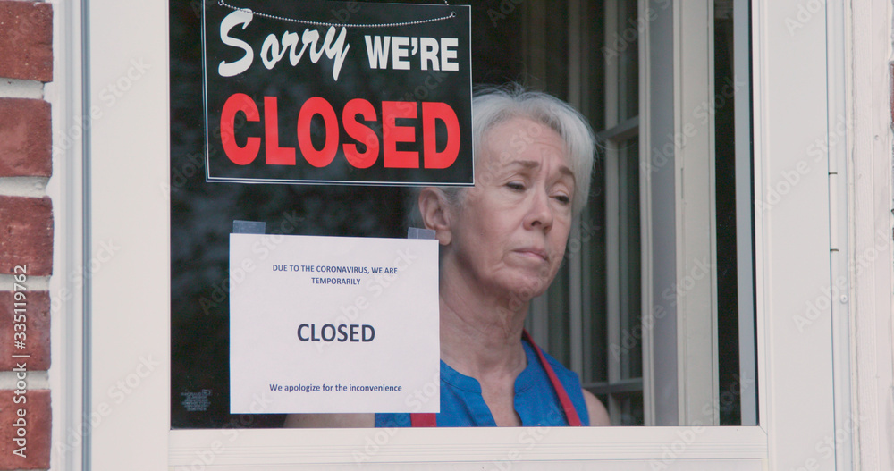 Fototapeta A worried mature small business owner turns the sign on her storefront from open to closed as a result of the shutdown issued because of the coronavirus.