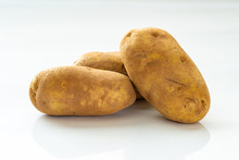 Close Up Of Three Russet Potatoes On White Background