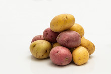 Pile Of Red And Yellow Bite Size Potatoes Over White Background