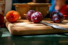 Cutting Board With Fresh Plums, Apricots And Bowl Of Olives