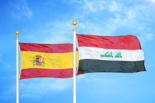 Spain And Iraq Two Two Flags On Flagpoles And Blue Cloudy Sky