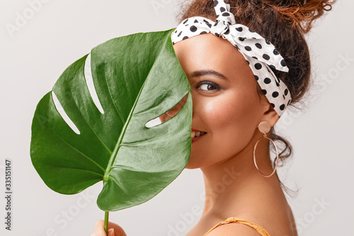 Carta da parati Beautiful African-American woman with tropical leaf on light background