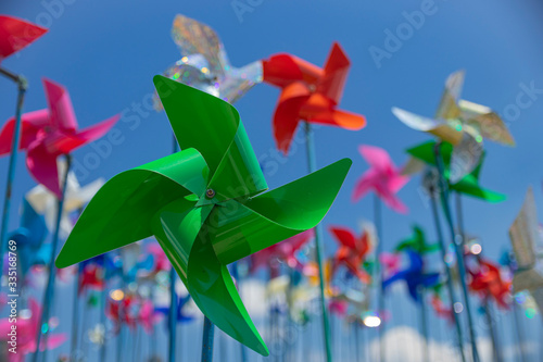 Green pinwheel standing against the backdrop of multicolored pinwheels Fototapet