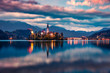 Dramatic morning view of Pilgrimage Church of the Assumption of Maria. Calm autumn sunrise on Bled lake, Julian Alps, Slovenia, Europe. Traveling concept background.