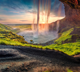 Populaк tourist destination - Seljalandsfoss waterfall, where tourists can walk behind the falling waters. Spectacular summer scene of Iceland, Europe. Beauty of nature concept background.