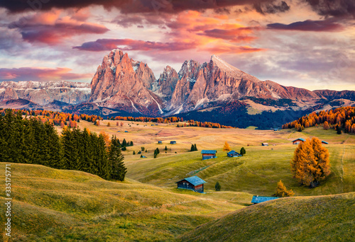 Fototapeta Unbelievable sunrise on Alpe di Siusi mountain plateau with beautiful yellow larch trees and Langkofel (Sassolungo) mountain on background. Autumn evening in Dolomite Alps, Ortisei locattion, Italy. obraz