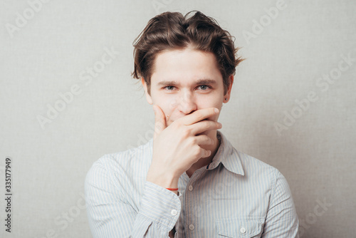 Photo young man with hand over his mouth, stunned and speechless