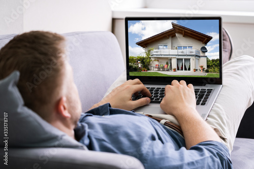 Fototapeta Man Selecting New House On Laptop At Home obraz