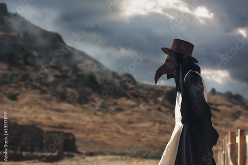 Obraz A man in historical masquerade costume of plague doctor in old gothic grange building of church. Epidemia protection costume. Pandemia horror mystical fantasy plague doctor - fototapety do salonu