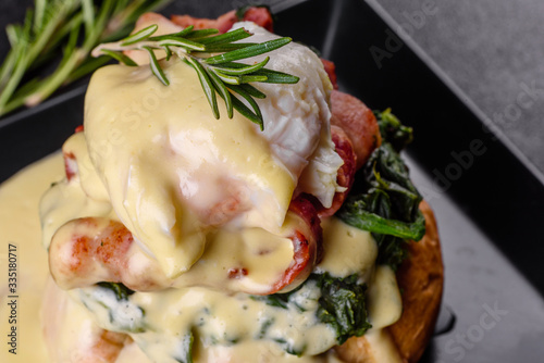 Photo Eggs benedict or eggs florentine on a black plate in the cafe
