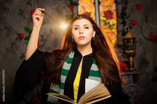 A young woman in a black mantle with a striped scarf around her neck casts a spell from a book and conjures with a wand of magic Fototapete