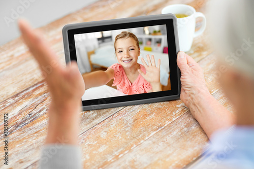 Obraz technology, communication and family concept - senior woman having video call with happy granddaughter on tablet computer at home - fototapety do salonu