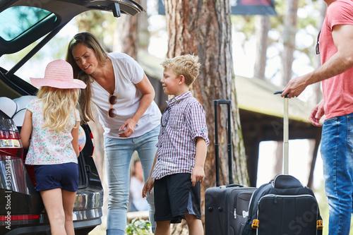 Fotografie, Obraz Eltern und Kinder laden Koffer in das Auto