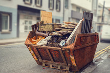 Old Rusty Dumpster Skip In A Street Fool Of Rubbish And Old Furniture, Selective Color. Nobody. Concept Getting Rid Of Old Junk.