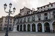 Arcades and clock tower in Piazza della Loggia, Brescia, Lombardy, Italy.