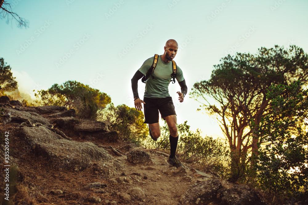 Fototapeta Man running on a rocky mountain trail