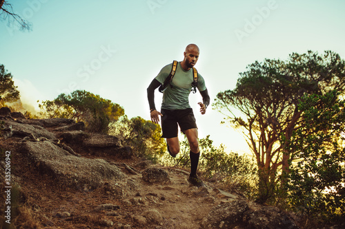 Leinwand Poster Man running on a rocky mountain trail
