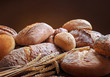 heap of various fresh baked bread with ears of wheat