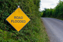 Yellow Road Sign On A Rural Road Warning That The Road Is Flooded