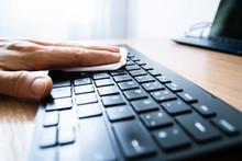 Man Wiping Keyboard With Sanit...