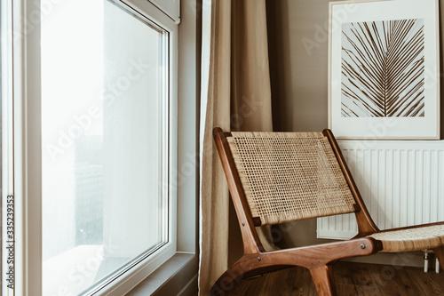 Obraz Modern interior design concept. Stylish rattan wooden chair, window, curtains. Minimal comfortable cozy living room. - fototapety do salonu