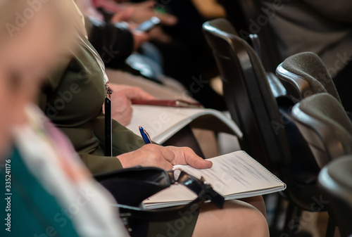 Man makes notes in a notebook while sitting at a press conference Fototapet