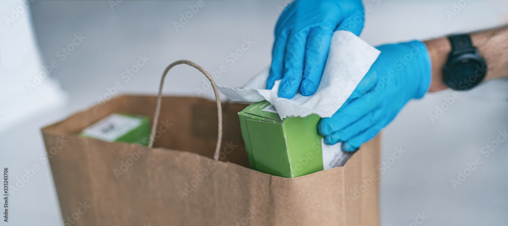 Fototapeta Coronavirus wiping down grocery packages after receiving home delivery wearing gloves, using disinfecting sanitizing wipes to wipe the surfaces clean. Cleaning of COVID-19 virus.