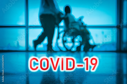 Obraz COVID-19 billboard red text on blue medical hospital background with doctor walking with disabled patient in wheelchair. - fototapety do salonu