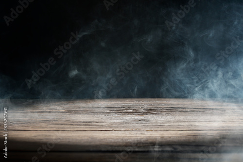 An old wooden table on a black background with smoke Canvas Print