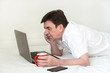 Man with laptop on bed in bedroom. Work from home during quarantine and self isolation. Concept of quarantine, pandemic, coronavirus, online work, education, mockup. Remote work from home.