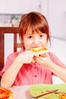 Funny portrait of cute little girl with pizza. Happy child having fun eating dinner.
