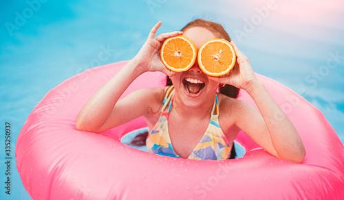 Happy girl with orange fruit having fun in pool Tablou Canvas