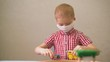 child in a medical mask plays with toys at the table. children in quarantine