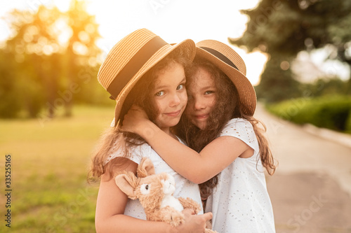 Fototapeta Adorable little sisters hugging in park