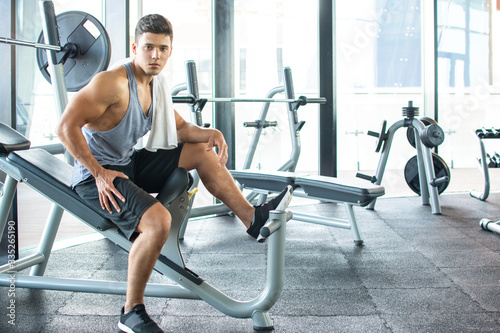 Fotografia Handsome young man resting on exercise machine after workout with towel around h