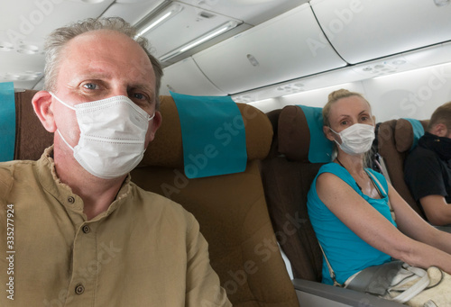 Woman and man in medical protective mask in the airplane Canvas Print