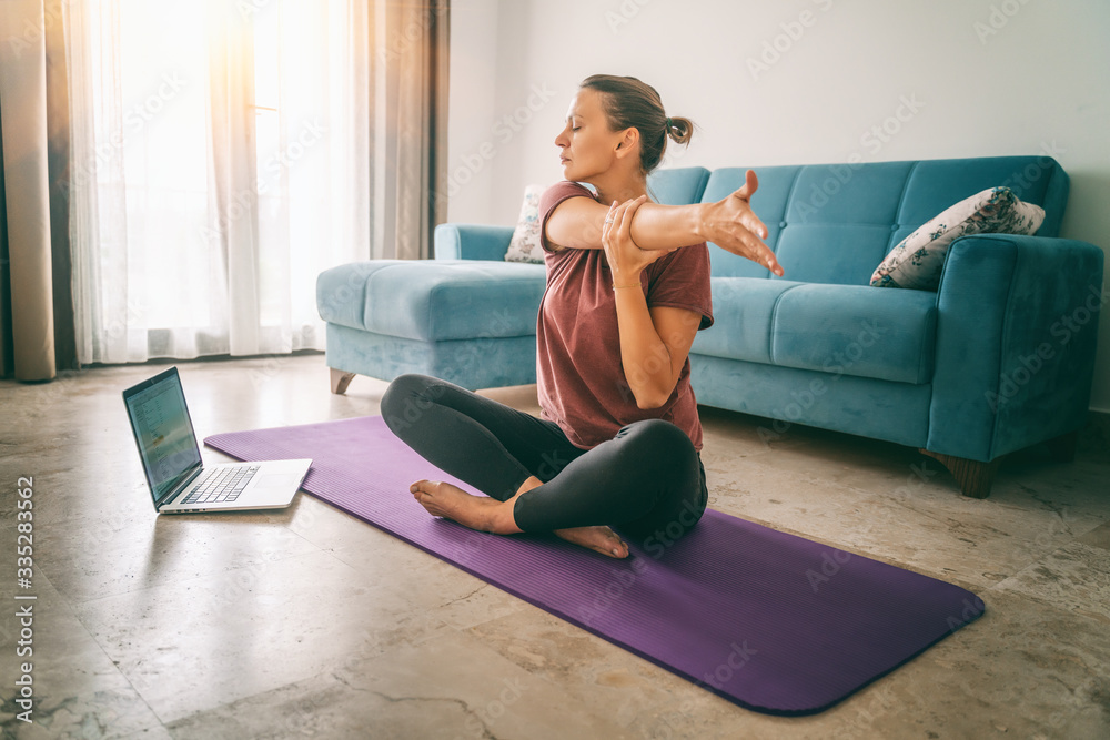 Fototapeta Attractive young woman doing yoga stretching yoga online at home. Self-isolation is beneficial, entertainment and education on the Internet. Healthy lifestyle concept - obraz na płótnie