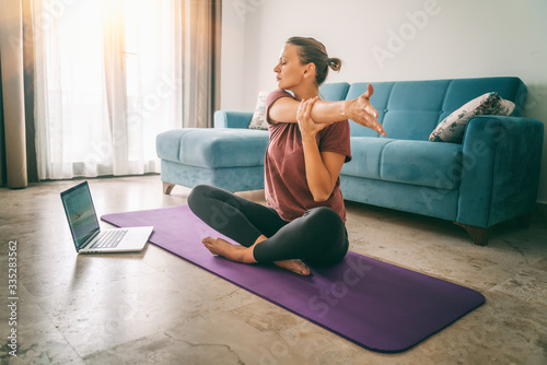 Fototapeta Attractive young woman doing yoga stretching yoga online at home. Self-isolation is beneficial, entertainment and education on the Internet. Healthy lifestyle concept obraz