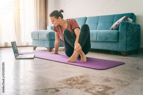 Fototapeta Attractive young woman doing yoga stretching yoga online at home. Self-isolation is beneficial, entertainment and education on the Internet. Healthy lifestyle concept obraz na płótnie