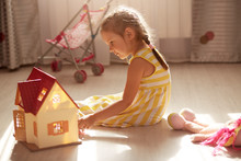 Close Up Portrait Of Beautiful Toddler Girl With Pigtails Sitting On Floor Playing With Toy Doll House, Toy Baby Carriage Near Window On Background., Female Kid Wearing Yellow Dress. Childhood Concept