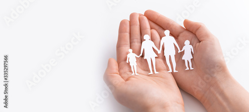 Fotografía Family care concept. Hands with paper silhouette on table.