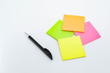 Pen And Note Pads In Day Glo Colors Isolated Against A Plain White Background.