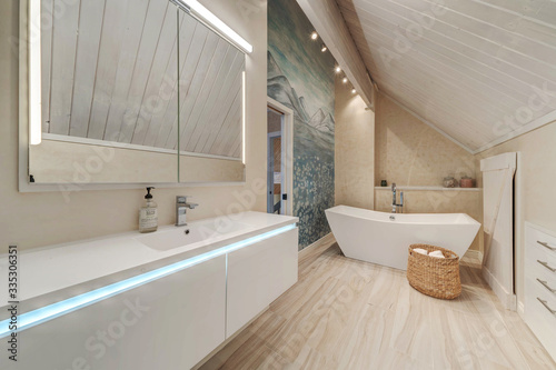 Fototapeta Luxury bathroom interior with free standing modern tub, mural, vaulted wooden ceiling, large and bright. obraz