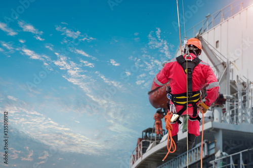 Photo Rope access Abseiling Safety man worker Abseiling from building structure steel with safety harness and wearing equipment protective PPE safety concept on blue sky background