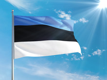 Estonia National Flag Waving In The Wind Against Deep Blue Sky. High Quality Fabric. International Relations Concept.