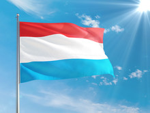 Luxembourg National Flag Waving In The Wind Against Deep Blue Sky. High Quality Fabric. International Relations Concept.