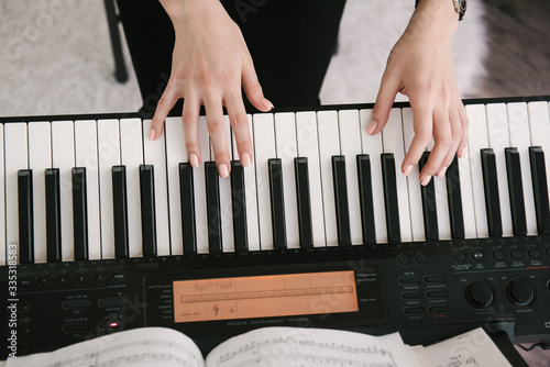 Canvas Print women's manicured hands play music on the piano